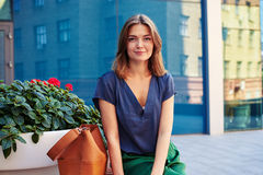 Close-up of smiling elegant woman on bench on the background of. Close-up of charming smiling elegant woman sitting on bench with flower pot on the background of Royalty Free Stock Images