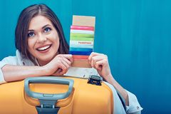 Close up smiling face portrait of young woman holding passport w. Ith ticket for travel, big yellow suitcase Royalty Free Stock Photos