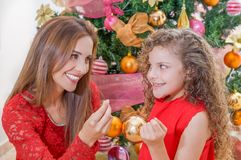 Close up of smiling family decorating Christmas tree, mom and daughter, family christmas concept.  Stock Images