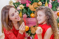 Close up of smiling family decorating Christmas tree, mom and daughter, family christmas concept.  Royalty Free Stock Image