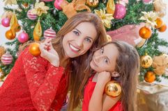 Close up of smiling family decorating Christmas tree, mom and daughter, family christmas concept.  Stock Photos