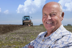Close up of smiling farmer in field with tractor and plough in background Royalty Free Stock Photography