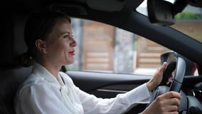 Businesswoman talking on in-car speakerphone. Close-up of smiling female chatting by phone in car using bluetooth hands free technology. Pretty woman in business stock video