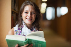 Close up of a smiling female student in library. Close up portrait of a smiling female student in the library Royalty Free Stock Image