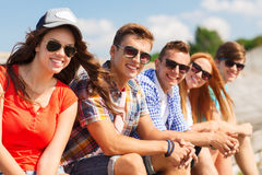 Close up of smiling friends sitting on city street Royalty Free Stock Photo