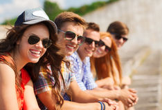 Close up of smiling friends sitting on city street Royalty Free Stock Photos
