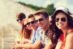 Close up of smiling friends sitting on city street Royalty Free Stock Image