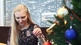 Close up of smiling girl hanging balls on Christmas tree. With skyscrapers on the background. The woman smiles and decorates the fir tree with colorful toys stock video footage
