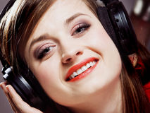 Close up smiling girl with headphones. Listen music on the grey background Stock Image