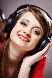 Close up smiling girl with headphones. Listen music on the grey background Royalty Free Stock Photography