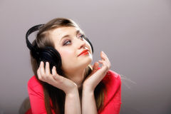 Close up smiling girl with headphones. Listen music on the grey background Royalty Free Stock Image