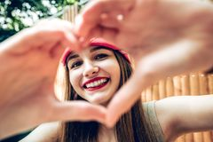Close up of smiling girl with healthy skin showing love sign. stock photos