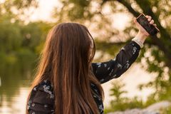 Cheerful girl making selfie on in park. Close up smiling girl photographing selfie on phone, girl is unfocused stock photos