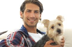 Close-up of a smiling guy stroking his dog while sitting in a large armchair. Royalty Free Stock Photos