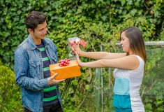 Close up of smiling and happy man holding a gift and flowers with his girlfriend stretching both arms ignoring him. Close up of smiling and happy men holding a Royalty Free Stock Photography