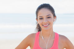 Close up of smiling healthy with earphones on beach Royalty Free Stock Photography
