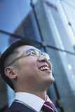 Close-up of smiling and laughing businessman looking up with glass reflection of skyscraper Stock Photo