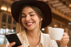 Close up of a smiling lovely girl in hat sitting at the cafe table indoors, holding cup of tea,. Using mobile phone stock photography