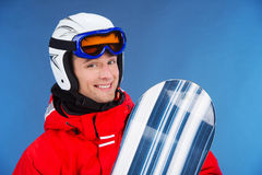Close up of smiling male snowboarder in helmet and mask. Standing with snowboard isolated over blue background Stock Photos