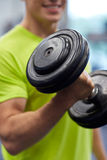 Close up of smiling man with dumbbell in gym Stock Photo