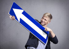 Close up of smiling man holding direction arrow sign. Stock Photography