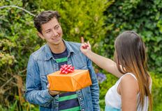 Close up of smiling man holding a gift and flowers with his girlfriend doing a middle finger sign, friendzone concept. Close up of smiling men holding a gift and Royalty Free Stock Image