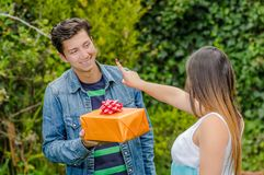 Close up of smiling man holding a gift and flowers and his girlfriend doing a not finger sign, friend zone concept. Close up of smiling men holding a gift and Stock Images