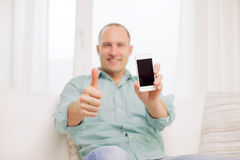 Close up of smiling man with smartphone at home Stock Image