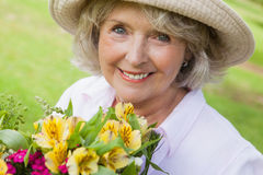 Close-up of smiling mature woman holding flowers at park Royalty Free Stock Images