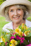 Close-up of a smiling mature woman holding flowers at park Stock Photography