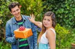 Close up of smiling man holding a gift and his girlfriend, stretching her arm ignoring him, friend zone concept. Close up of smiling men holding a gift and his Stock Image