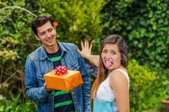 Close up of smiling man holding a gift and his girlfriend, stretching her arm ignoring him and woman doing a disgusting. Close up of smiling men holding a gift Stock Image