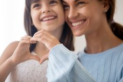 Loving mom and daughter show heart sign by hands stock photo