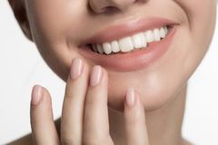 Positive cute girl is expressing gladness. Close up of smiling mouth and fingers of happy young lady enjoying her fresh skin. She is slightly touching her chin stock photos