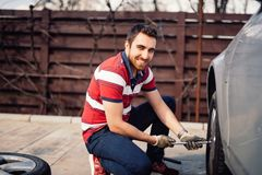 Close up smiling portrait of working man and changing tires using wrench, jack and hydraulic tools. Smiling portrait of working man and changing tires using royalty free stock photography