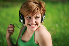 Close-up of smiling pretty girl listening to music. With headphones sitting on the grass in the park stock photo