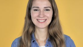 Close up of smiling pretty woman isolated on yellow background stock footage