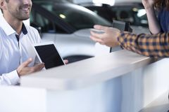 Close-up of smiling professional car seller with tablet offering stock images