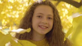 Close-up of a smiling redhead caucasian girl in mustard sweater looking at the camera. Child with long curly hair and