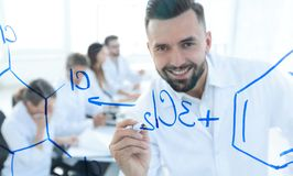 Close up of a smiling scientist writes a formula on the blackboard. In the lab Royalty Free Stock Image
