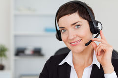 Close up of a smiling secretary calling. With a headset in her office Stock Photos