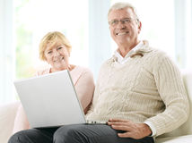 Close up of a smiling senior happy couple in front of a laptop Stock Images