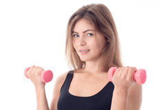 Close-up of a smiling sporty girl who holds in her hands the two dumbbells Royalty Free Stock Image