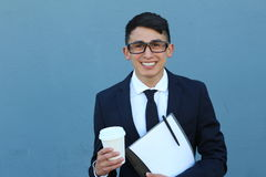 Close-up of smiling very young male on blue background with copy space holding books and to go coffee cup.  Royalty Free Stock Image