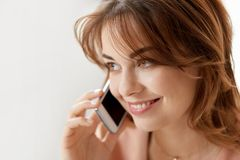 Close up of smiling woman calling on smartphone. Technology, communication and people concept - close up of smiling woman calling on smartphone Stock Photo