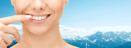Close up of smiling woman face pointing to teeth Stock Photography
