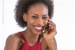 Close up of smiling woman on her phone against a white background Royalty Free Stock Image