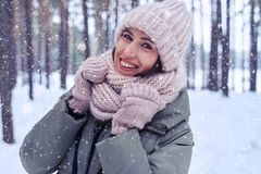 Close-up of smiling woman looking at the camera on a snowing col. Close-up of smiling woman wearing knitted warm scarf looking at the camera on a snowing cold Royalty Free Stock Photography