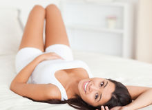 Close up of a smiling woman lying on bed Royalty Free Stock Images