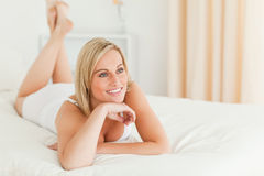 Close up of a smiling woman lying on her bed Stock Photo